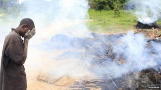 A Zimbabwean villager weeps in front of burning and demolished makeshift shelters at Manzou Farm in Mazowe - 8 January 2015