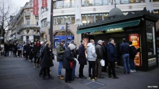 People queue to get a copy of satirical French magazine Charlie Hebdo in front of a kiosk in Paris on 14 January 2015.