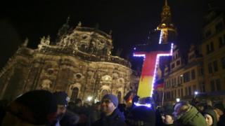 Participants hold a cross painted in the colours of German national flag during a demonstration called by anti-immigration group Pegida