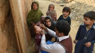 Pakistani polio vaccination worker Sher Khan (C) administers polio vaccine to a child in a poor neighbourhood that hosts Afghan refugees and internally displaced tribal people on the outskirts of Islamabad on December 29, 2014