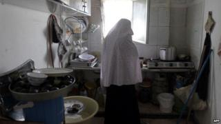 yrian refugee woman Umm Ammar cooks in a kitchen in her rented house in the Nazzal neighbourhood in Amman, Jordan, on May 30, 2012