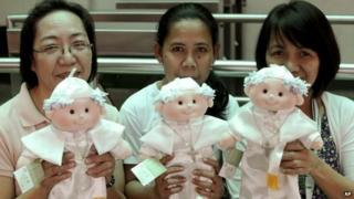Filipino devotees hold limited edition Pope Francis dolls that are sold by the De La Salle University in Manila, Philippines Wednesday, Jan. 14, 2015.