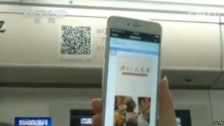 A person holding a phone to scan the barcode on the metro carriage