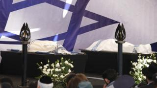 The bodies of two victims are placed on a platform at a cemetery in Jerusalem
