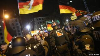 DRESDEN, GERMANY - JANUARY 12: Supporters of the Pegida movement wave German while strolling past riot police through the city center during their weekly protest on January 12, 2015 in Dresden, Germany
