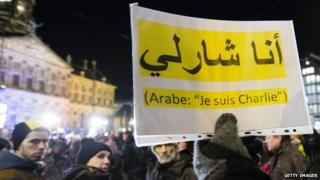 """People hold up """"Je Suis Charlie"""" placard in Arabic"""