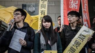 Student activist Joshua Wong (R) and other students display pro-democracy placards outside the Wanchai police station in Hong Kong on January 16, 2015