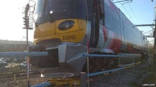 Yellow engineering trolley underneath the train after the collision