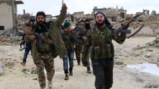Opposition fighters walk in the Syrian town of Aleppo after they reportedly re-took control of the area from pro-government forces on 7 January 2015