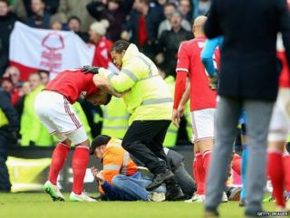 A man is tackled by stewards after the final whistle