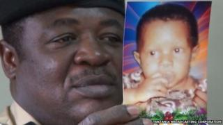 A policeman holds up a picture of missing albino girl Pendo Emmanuelle Nundi