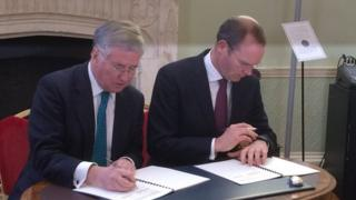 Michael Fallon (left) and Simon Coveney sign a memorandum of understanding at Dublin Castle