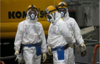 Workers prepare themselves prior to operate in front of Unit Three under the decommissioning of its reactors at tsunami-crippled Tokyo Electric Power Co.'s Fukushima Daiichi Nuclear Power Plant in Okuma, Fukushima Prefecture, northern Japan, 11 December 2014