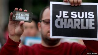 A man holding a Je Suis Charlie sign
