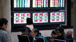 Investors look through stock information at a trading hall of a securities firm in Shanghai