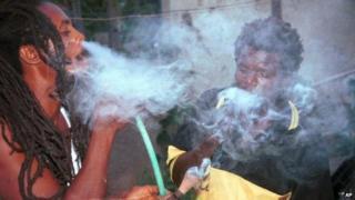 Jah P., left, and Jah Henry, smoke marijuana from a chillum pipe in Kingston, Jamaica, Wednesday, Aug. 18, 1999.