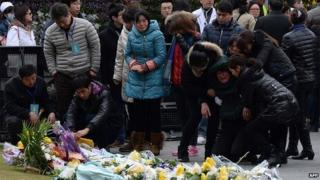 Family members mourn for the victims of a stampede by new year's revellers on the seventh day after the accident in Shanghai's historic riverfront in Shanghai on January 6, 2015.