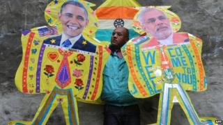 An Indian kitemaker poses with kites with images of US President Barack Obama and Indian PM Narendra Modi (in Amritsar on January 21, 2015.