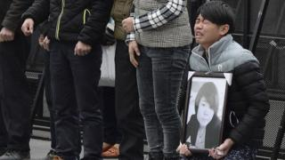 A man holds a portrait of a victim of the New Year's Eve stampede in Shanghai next to other mourners on 6 January 2015.