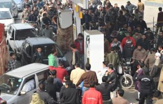 Pakistani motorcyclists queue at a petrol station in Lahore on January 20
