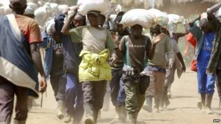 Men carrying ore from a mine not far from Goma in DR Congo, which borders Rwanda