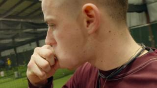 Man stuffing dip into a bulging cheek