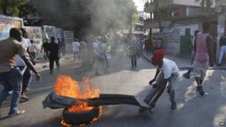 Protesters set a tyre on fire in Port-au-Prince. Photo: 23 January 2015