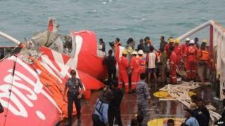 In this photograph taken on January 10, 2015, wreckage from AirAsia flight QZ8501 is lifted into a ship at sea south of Borneo island.