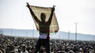 Kurdish people flash the V for victory sign during a celebration rally near the Turkish-Syrian border at Suruc, in Turkey's Sanliurfa province, on Tuesday