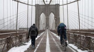 Commuters make their way across the Brooklyn Bridge after a snow storm in New York January 27, 2015.