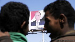 Yemeni men under a banner showing former Yemeni President Abd Rabu Mansour Hadi in Sana'a, Yemen, on 23 January 2015