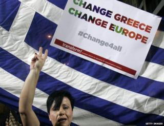 Syriza supporter holds flag and placard (22 Jan)