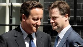 David Cameron and Nick Clegg pass each other outside Downing Street