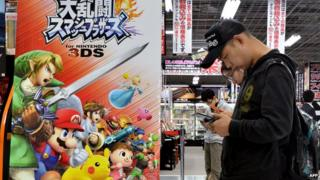 Customers play video games at an electric shop in Tokyo.