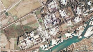 Nuclear reactor, North Korea. Satellite image of a five-megawatt nuclear reactor (centre left) in Yongbyon in North Korea. The steam coming from the white tower (lower left) indicates the reactor is in operation, since being restarted in early 2003. Photographed on 7 November 2004 by the Quickbird satellite.