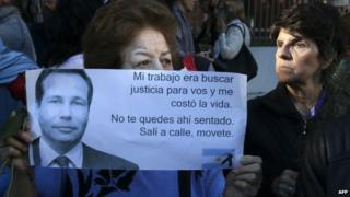 A woman holds a sign during the funeral of prosecutor Alberto Nisman, January 29, 2015.