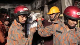 Fire-fighters carry the body of a victim of a fire in Dhaka. Photo: 31 January 2015