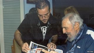 Former Cuban President Fidel Castro and Randy Perdomo look at a newspaper during a meeting in Havana in this picture provided by Cubadebate on 2 February 2015
