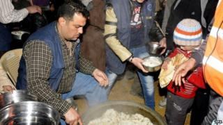 internally displaced Syrians receiving food aid after being evacuated from Ghouta, Damascus, Syria, 17 January 2015