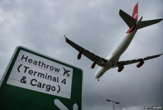 Plane comes in to land over road sign for Heathrow airport