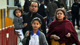 Pakistani school children are picked up by their parents after unknown culprits threw a hand grenade at a school, in Karachi, Pakistan, 3 February 2015
