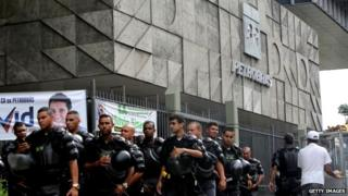 "Military Police (PM) walk out after guarding Brazil""s government-run oil company Petrobras during a protest in front of Petrobras headquarters on February 4, 2015"