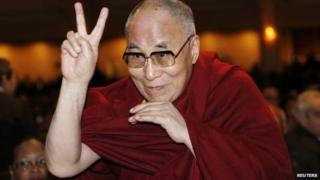The Dalai Lama directs a peace sign toward the head table, where U.S. President Barack Obama was seated, during the National Prayer Breakfast in Washington 5 February 2015