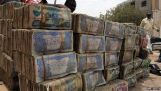 Somali money changer talks on phone on March 8, 2012 next to piles of banknotes