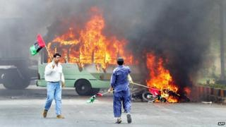 Pakistani opposition parties activists walk alongside burning vehicles after clashes erupted between the government and opposition parties supporters in Karachi, 12 May 2007