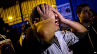 A bereaved father grieves for his dead sons at the Zynhom morgue in Cairo on February 8, 2015