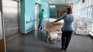 A nurse and another member of hospital staff pushing a trolley bed in a hospital