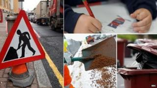 Traffic sign, child writing, road being dug up, and bins waiting to be emptied