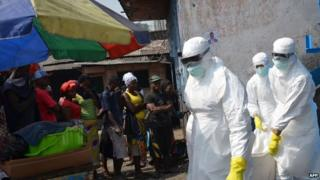 Red Cross workers, wearing protective suits, carry the body of a person who died from Ebola during a burial with relatives of the victims of the virus, in Monrovia, 5 January 2015