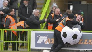 Stewards eject a Grimsby Town fan from The New Lawn
